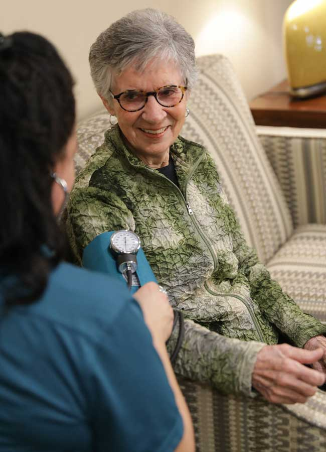 A Heritage OnCare staff member taking blood pressure.