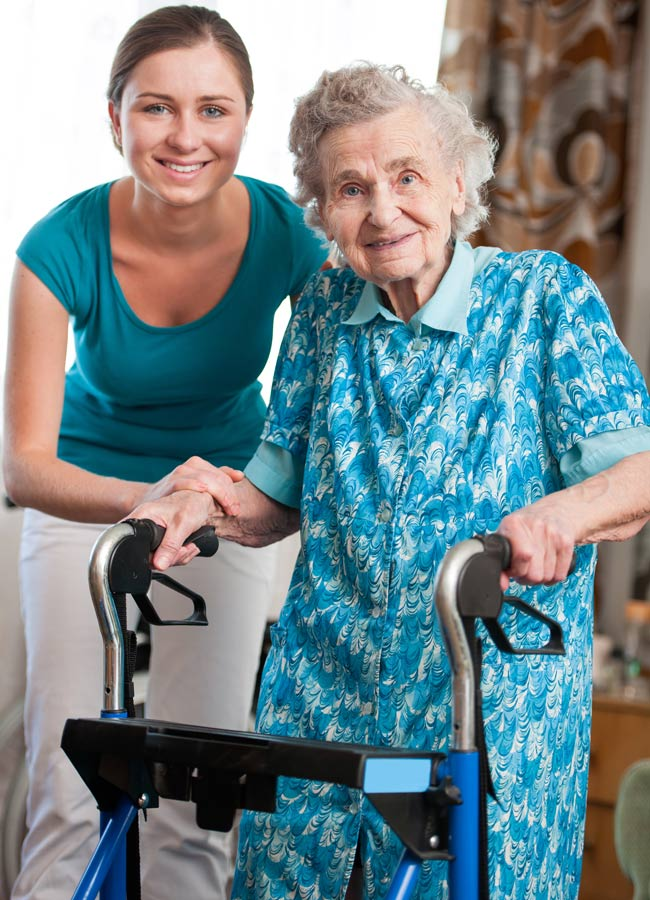 Home Health CNA standing next to senior woman with a walker