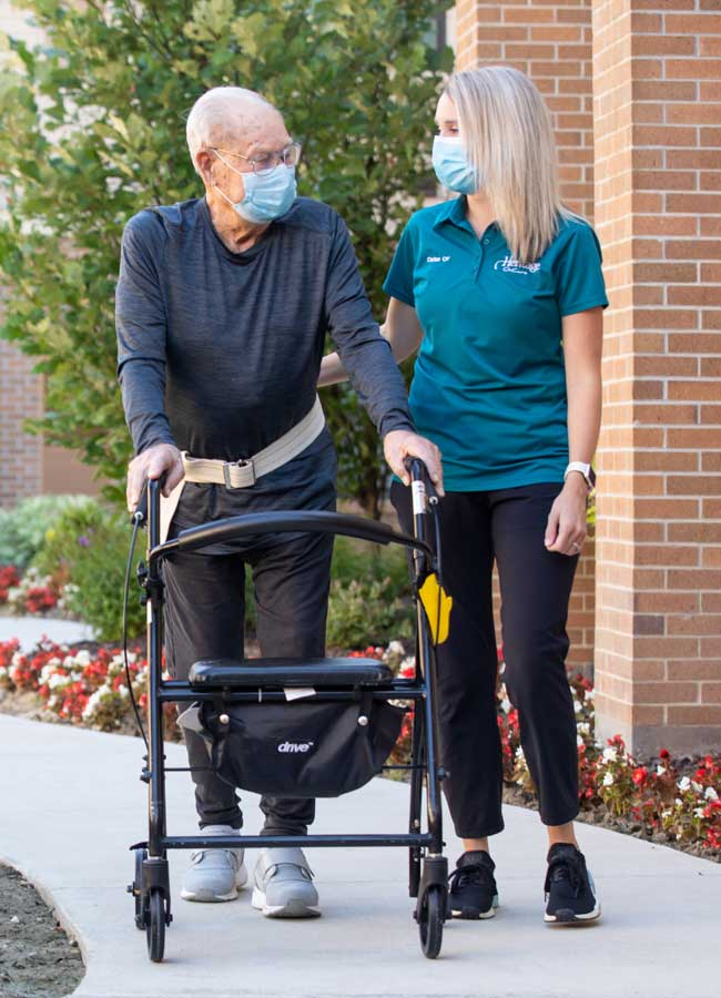 RN walking with senior patient outside of home