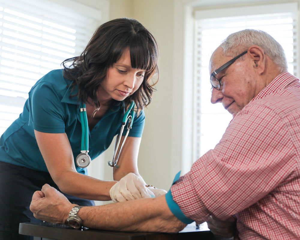 Home Health Nurse drawing blood from forearm of older adult man