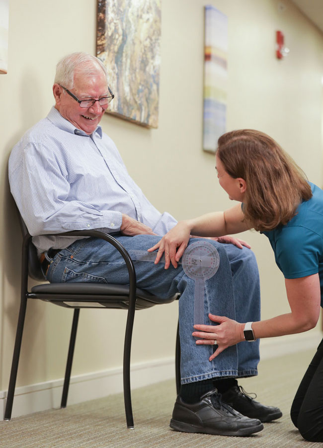 Occupational Therapist educating senior patient with his therapy