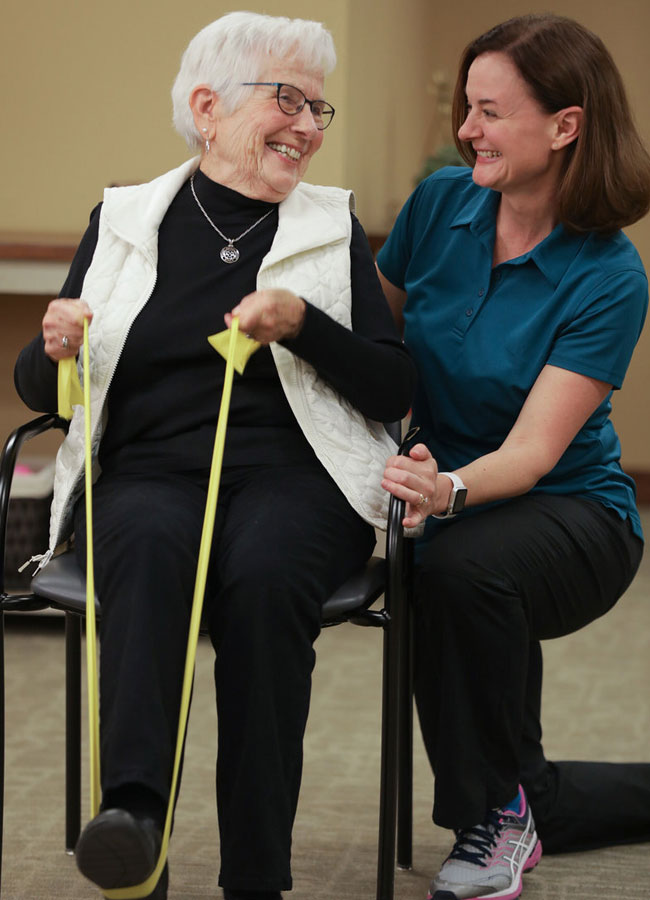 Physical Therapist smiling at elderly patient as she does her leg exercises