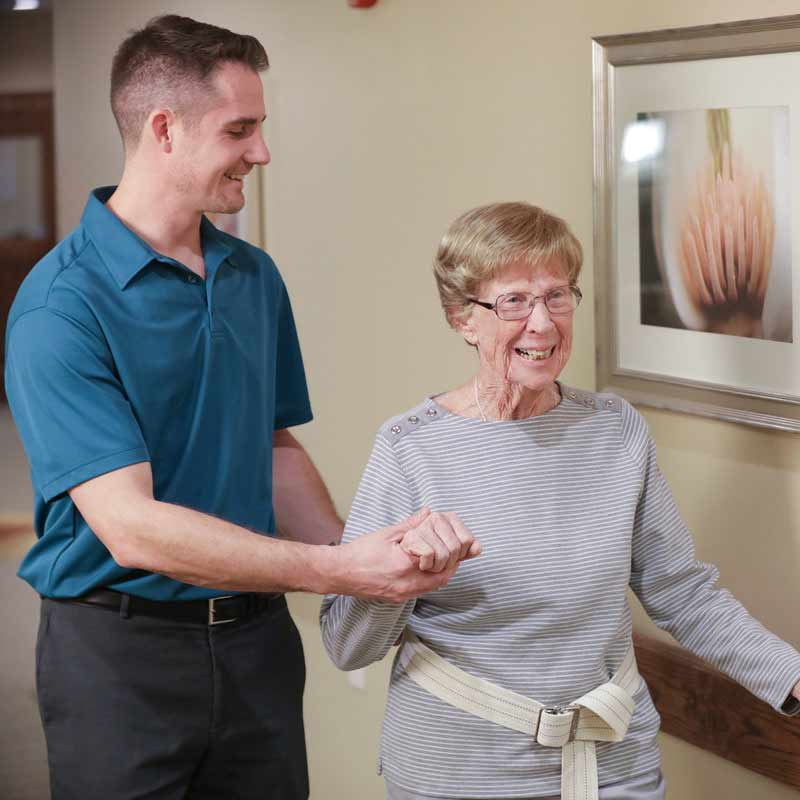 Male nurse assisting older adult woman as she walks down the hall in her home
