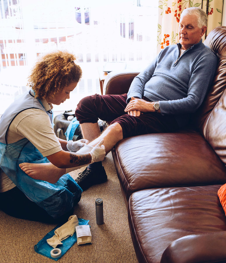 A nurse assisting a patient with wound care.